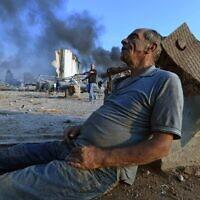 Un homme est assis au sol en attendant de l'aide au port de Beyrouth après l'énorme explosion qui a frappé le coeur de la capitale libanaise le 4 août 2020.  (Photo by - / AFP)