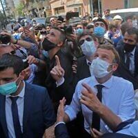 Le président français Emmanuel Macron discute avec la population lors de sa visite du quartier de Beyrouth de Gemmayzeh, qui a subi d'importants dégâts lors de l'explosion massive dans la capitale libanaise, le 6 août 2020. (Autorisation : AFP)