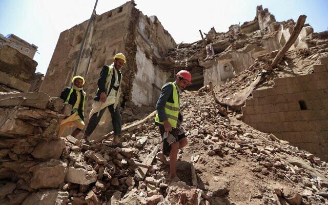 Des ouvriers yéménites enlèvent les décombres avant les travaux de restauration d'un bâtiment classé par l'UNESCO détruit suite à de fortes pluies, dans la vieille ville de la capitale yéménite Sanaa, le 12 août 2020. (Mohammed HUWAIS / AFP)