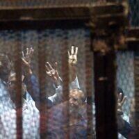Sur cette photo prise le 21 avril 2015, les hauts responsables de Frères musulmans Issam al-Eriane (gauche) et Mohammed Beltagi (droite) font des gestes avec d'autres accusés depuis leur box lors de leur procès en compagnie de 14 autres personnes. (Photo par Mohamed el-Shahed / AFP)