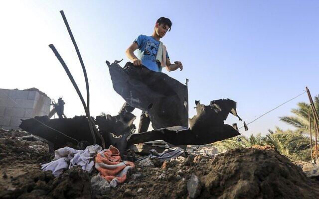 Un jeune inspecte les décombres et autres dégâts sur un toit suite à une frappe israélienne, à l'est du camp palestinien de réfugiés d'al-Bureij, dans le centre de Gaza, le 15 août 2020 (Crédit : MAHMUD HAMS / AFP)