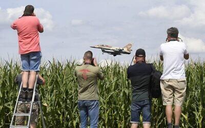 Des amateurs d'aviation photographient l'approche d'un bombardier israélien F-16 à la base aérienne de Noervenich, en Allemagne de l'Ouest, le 17 août 2020. (Roberto Pfeil / dpa / AFP)