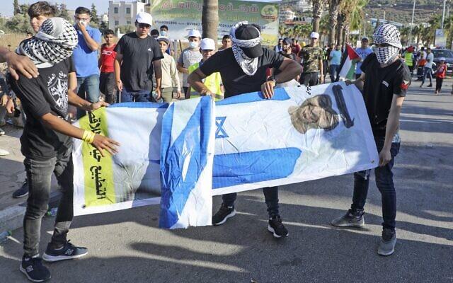 Des jeunes Palestiniens tiennent une affiche du prince héritier d'Abou Dhabi, le cheikh Mohammed bin Zayed al-Nahyan, alors qu'ils protestent contre la décision des Émirats arabes unis de normaliser leurs relations avec Israël, dans le village de Turmus'ayya près de la ville de Ramallah en Cisjordanie, le 19 août 2020. (JAAFAR ASHTIYEH / AFP)