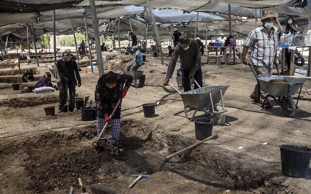 Des ouvriers fouillent un site où d'un tas de pièces d'or datant du califat abbasside a été mis au jour, sur un site archéologique près de Tel Aviv. (Crédit : Heidi Levine / POOL / AFP)