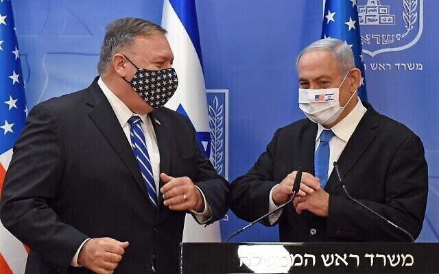 Le secrétaire d'État américain Mike Pompeo et le Premier ministre Benjamin Netanyahu se saluent du coude, avant un point presse après leur rencontre à Jérusalem le 24 août 2020. (Crédit : DEBBIE HILL / POOL / AFP)