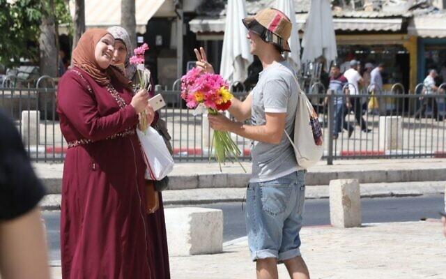 Un activiste du groupe Tag Meir, un groupe israélien financé par le New Israel Fund, donne des fleurs dans la lutte contre le racisme à Jérusalem, le 1er juin 2019 (Crédit : NIF/Yossi Zamir via JTA)