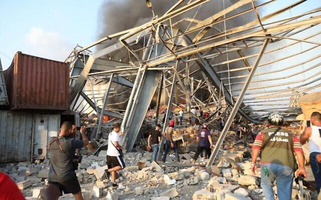 Des gens sur le site d'une explosion survenue dans la capitale libanaise Beyrouth, le 4 août 2020. (Crédit : Anwar AMRO / AFP)