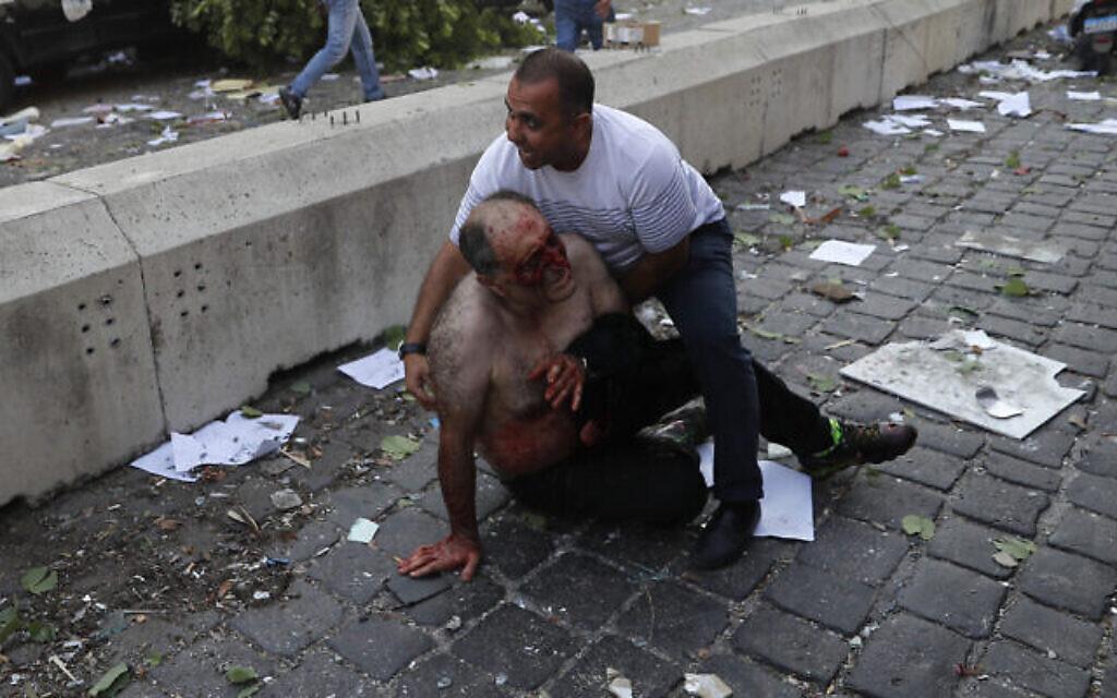 Un Libanais aide un blessé à Beyrouth, après une explosion sur le port, le 4 août 2020. (Crédit : AP Photo/Hussein Malla)