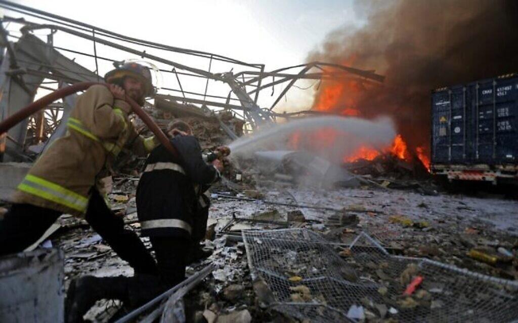 Des pompiers libanais éteignent un incendie sur la scène d'une explosion dans le port de Beyrouth, capitale du Liban, le 4 août 2020. (Crédit : STR / AFP)