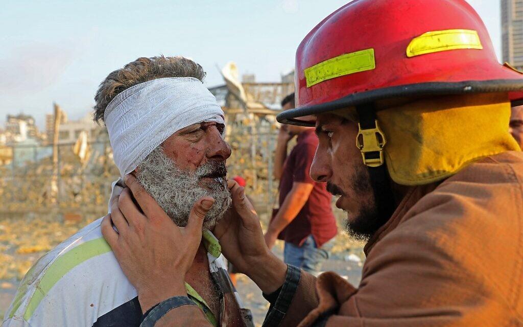 Un blessé est examiné par un pompier aux abords du site d'une explosion à Beyrouth, le 4 août 2020. (Crédit :  Anwar AMRO/AFP)