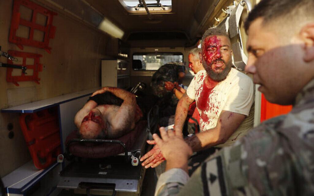 Un soldat libanais, à droite, avec des blessés dans une ambulance, sur les lieux de l'explosion qui a frappé le port de Beyrouth, au Liban, le mardi 4 août 2020. (Crédit : AP Photo / Hussein Malla)