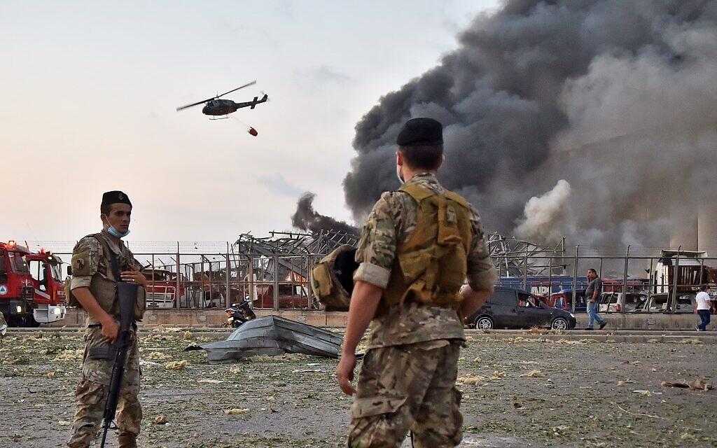 Des soldats libanais regardent un hélicoptère éteindre un incendie sur la scène d'une explosion dans le port de Beyrouth, capitale du Liban, le 4 août 2020. (Crédit : STR / AFP)
