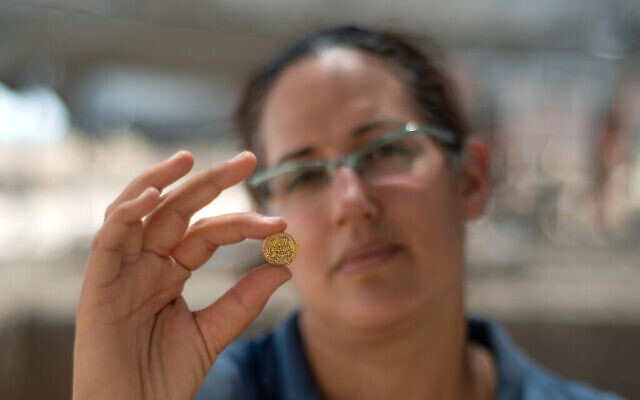 Liat Nadav-Ziv, directrice des fouilles, tient une pièce d'or. (Crédit : Yoli Schwartz, Israel Antiquities Authority)