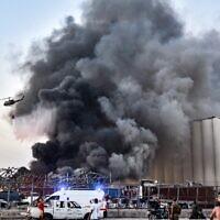 Un hélicoptère éteint un feu sur le site d'une explosion au port de la capitale libanaise Beyrouth, le 4 août 2020. (Crédit : STR / AFP)