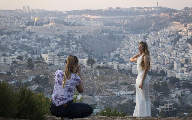 Une jeune femme israélienne en robe de mariée est photographiée avec en arrière-plan un panorama de la Vieille Ville de Jérusalem, le 8 août 2019. (Hadas Parush/Flash90)
