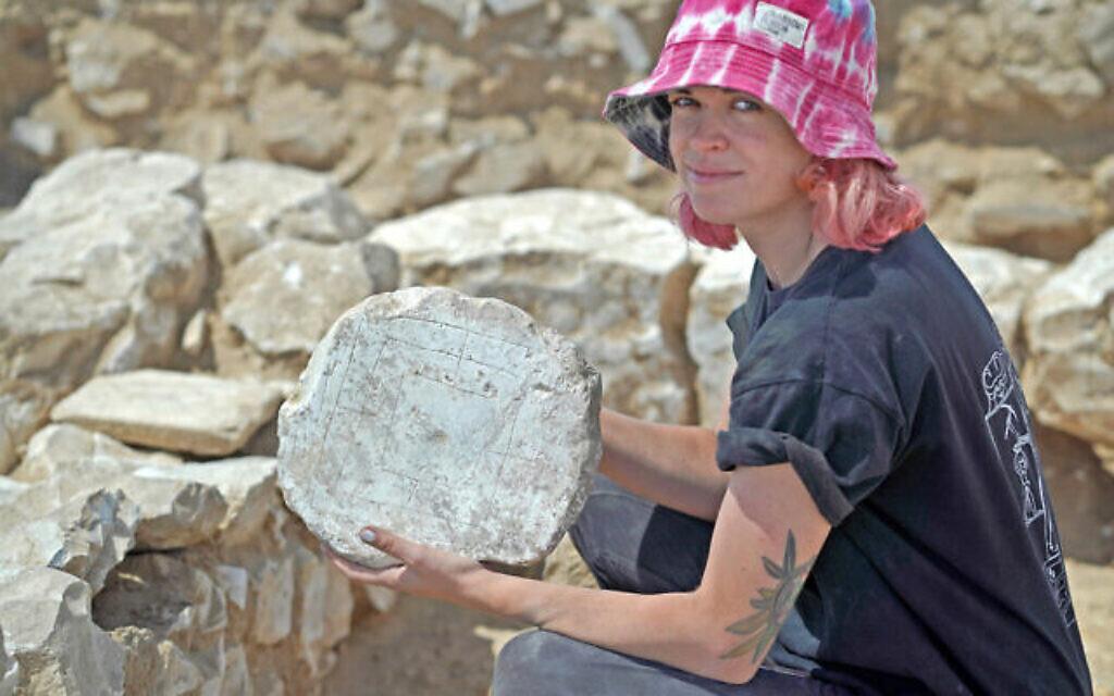 """La lycéenne Jenny Vasiutin tient entre ses mains le jeu du """"Moulin"""" trouvé pendant des fouilles menées par l'Autorité israélienne des antiquités à Rahat, ville bédouine du désert du Negev, (Crédit :Emil Aladjem/Israel Antiquities Authority)"""