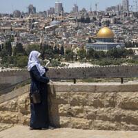 Une femme musulmane porte un masque et des gants sur le Mont des Oliviers à Jérusalem-Est, qui surplombe le Dôme du Rocher et le complexe de la mosquée Al-Aqsa sur le Mont du Temple, qui reste fermé pour empêcher la propagation du coronavirus pendant le mois sacré du Ramadan, le vendredi 1er mai 2020. (AP Photo/Ariel Schalit)