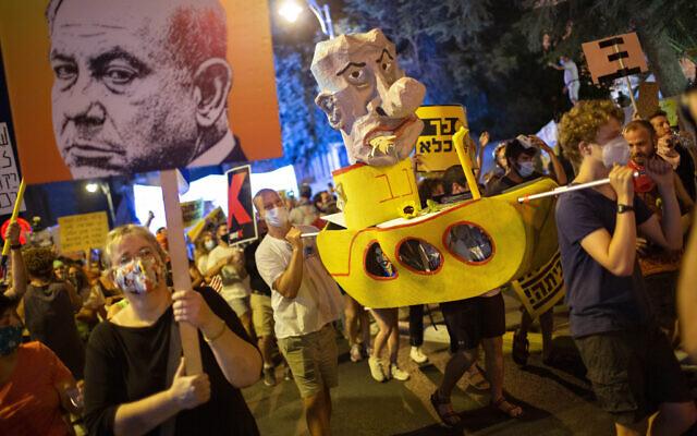 Des manifestants scandent des slogans et brandissent des pancartes lors d'un rassemblement contre le Premier ministre Benjamin Netanyahu devant sa résidence à Jérusalem, le samedi 1er août 2020. (AP Photo/Oded Balilty)