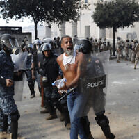 La police anti-émeute libanaise arrête un manifestant anti-gouvernemental, qui tentait d'atteindre le bâtiment du Parlement, lors d'une manifestation contre les élites politiques et le gouvernement, à Beyrouth, au Liban, le 8 août 2020. (AP Photo/Hussein Malla)