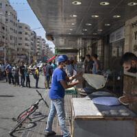 Des Palestiniens font la queue devant une boulangerie pour acheter du pain pendant le blocus de 48 heures imposé suite à la découverte des premiers cas de coronavirus dans la bande de Gaza, le 25 août 2020. (AP/Khalil Hamra)