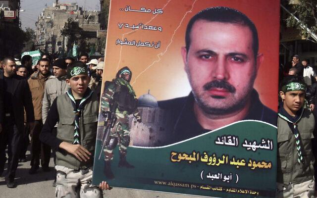Des Palestiniens brandissent une photo de Mahmoud al-Mabhouh, tandis que d'autres portent son cercueil, à gauche, lors de son cortège funèbre à Yarmouk, près de Damas, en Syrie, le 29 janvier 2010. (AP Photo/Bassem Tellawi/Fichier)