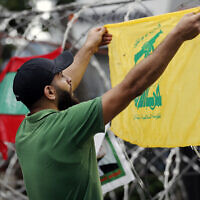 Un partisan du Hezbollah scande des slogans en brandissant le drapeau de l'organisation durant une manifestation contre l'intervention américaine dans les affaires du Liban, près de l'ambassade des Etats-Unis à Aukar, au nord-est de Beyrouth, le 10 juin 2020 (Crédit :  AP Photo / Hussein Malla)