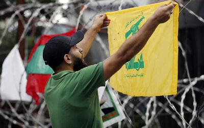 Un partisan du Hezbollah scande des slogans en brandissant le drapeau de l'organisation terroriste durant une manifestation contre l'intervention américaine dans les affaires du Liban, près de l'ambassade des Etats-Unis à Aukar, au nord-est de Beyrouth, le 10 juin 2020. (Crédit : AP Photo / Hussein Malla)