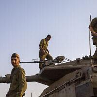 Des soldats israéliens travaillent sur des tanks aux abords de la frontière avec le Liban, le 28 juillet 2020 (Crédit : AP Photo/Ariel Schalit)