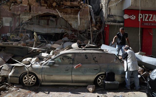 Des gens inspectent leur voiture, endommagée par la gigantesque explosion de la veille dans le port maritime de Beyrouth, au Liban, le 5 août 2020. (AP/Bilal Hussein)