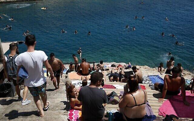 Des gens s'attroupent sur la plage de Limanakia Vouliagenis dans le sud d'Athènes, le 6 août 2020. (AP Photo / Thanassis Stavrakis)