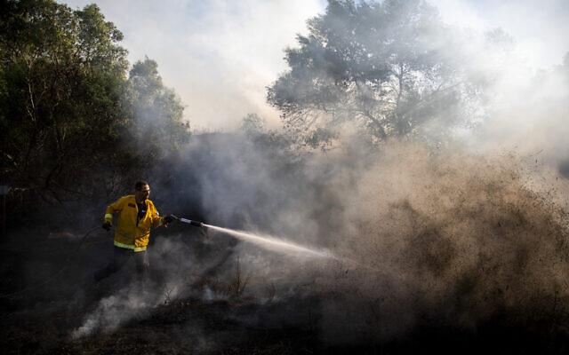 Un pompier tente d'éteindre un incendie déclenché par un engin incendiaire lancé depuis la bande de Gaza, dans le kibboutz Kfar Aza à la frontière avec Gaza, le 24 août 2020. (AP/Ariel Schalit)