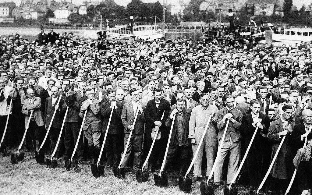 Des ouvriers avec des pelles écoutent Adolf Hitler parler alors que les travaux commencent sur la Reichsautobahn (autoroute) de Francfort-sur-le-Main à Heidelberg, le 23 septembre 1933. (AP Photo)