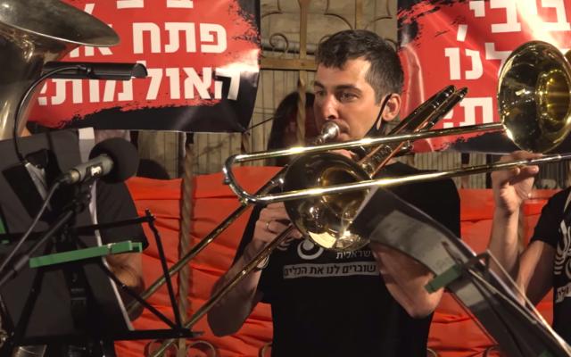 Un musicien de l'orchestre philharmonique d'Israël lors d'une manifestation contre le Premier ministre, rue Balfour à Jérusalem. (Crédit : capture d'écran Israel Philharmonic / Facebook)