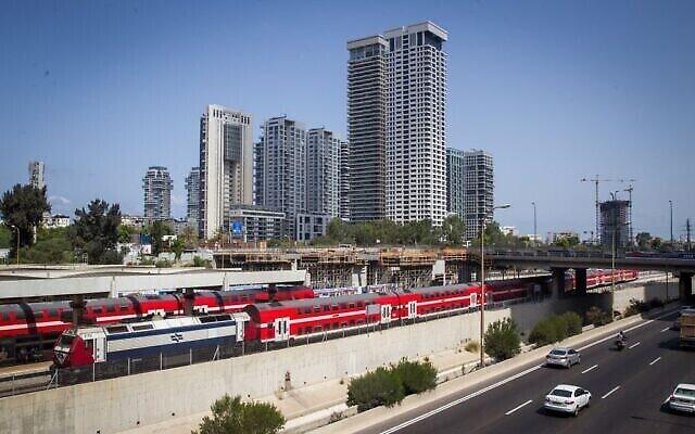 Un train de la Compagnie de chemins de fer israélienne passe à côté de la voie rapide Ayalon, près de la gare centrale de la rue Arlozorov à Tel Aviv, le 23 août 2016. (Crédit : Miriam Alster / Flash90)