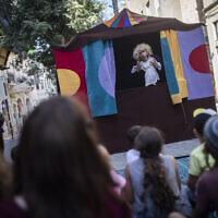 Des artistes de rue divertissent les enfants en vacances d'été sur Ben Yehuda Street dans le centre de Jérusalem, le 13 août 2019 (Crédit : Hadas Parush/Flash90)