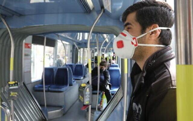 Des Israéliens portant des masques dans un bus à Jérusalem, le 17 mars 2020. (Yossi Zamir/Flash90)