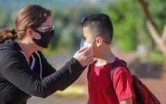 Un enfant israélien portant un masque sur le chemin de l'école au Moshav Yashresh, le 3 mai 2020. (Crédit: Yossi Aloni / Flash90)