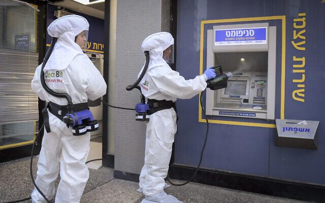 Des agents de nettoyage désinfectent un distributeur automatique de billets dans une banque à Ramat Gan, 3 juin 2020. (Flash90)
