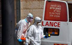 Employés du Magen David Adom portant des équipements de protection après avoir évacué un homme soupçonné d'être porteur du Coronavirus au centre médical Hadassah Ein Kerem à Jérusalem, le 20 juillet 2020. (Autorisation : Olivier Fitoussi / Flash90)