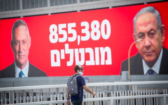 Un homme portant un masque passe devant une affiche montrant le Premier ministre Benjamin Netanyahu, à droite, et le ministre de la Défense et Premier ministre d'alternance Benny Gantz, à gauche, avec les chiffres du chômage actuels à Tel Aviv, le 22 juillet 2020 (Crédit : Miriam Alster/Flash90)