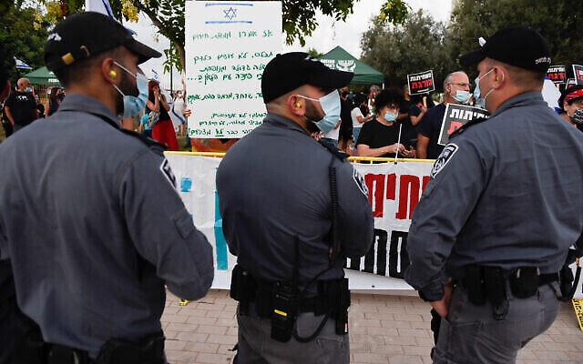 Des agents de police devant des manifestants protestant contre le Premier ministre Benjamin Netanyahu près de sa résidence située dans la ville côtière de Césarée, le 8 août 2020 (Crédit : Meir Vaknin/Flash90)
