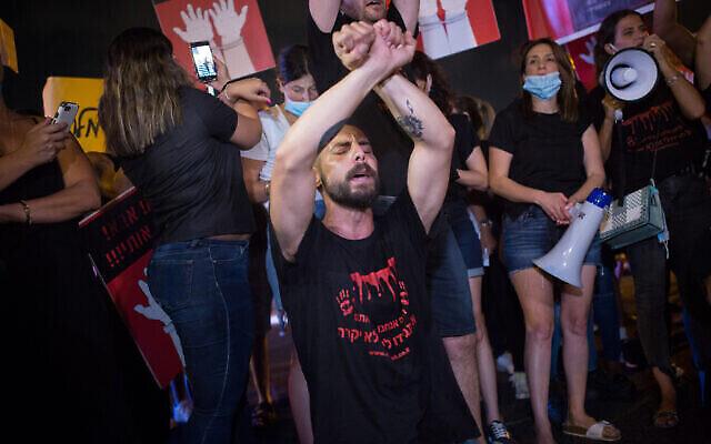 Des parents d'enfants de moins de 3 ans et d'autres manifestants bloquent une route pour protester contre la directrice et les employés d'une garderie de Ramle, soupçonnés d'avoir maltraité des enfants, à Tel Aviv, le 12 août 2020 (Autorisation : Miriam Alster / Flash90)