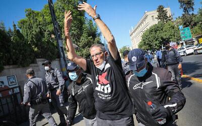 La police éloigne Carmi Gillon, un ancien chef du Shin Bet, d'un campement de protestation devant la résidence officielle du Premier ministre, le 20a août 2020. (Crédit : Olivier Fitoussi/Flash90)