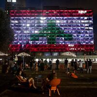 La municipalité de Tel Aviv, sur la place Rabin, est illuminée avec le drapeau libanais en solidarité avec les victimes de l'explosion du port de Beyrouth, le 5 août 2020. (Miriam Alster/Flash90)