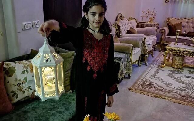 Un membre de la famille Abu Sbeih de Jérusalem-Est honore une tradition du Ramadan de brandir une lanterne dans le salon, avant la démolition de la maison familiale. (Iyad Abu Sbeih)