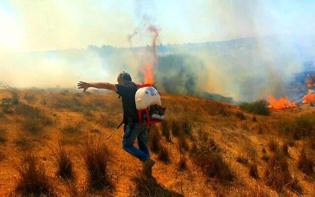 Un pompier cherche à éteindre un incendie causé par un ballon incendiaire envoyé de Gaza vers les communautés frontalières israéliennes, le 26 août 2020. (Crédit : Eshkol Regional Council)