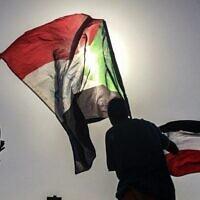 Des manifestants soudanais défilent avec des drapeaux nationaux alors qu'ils se rassemblent lors d'une manifestation pour demander la création d'organes civils pour mener la transition vers la démocratie, devant le quartier général de l'armée dans la capitale soudanaise de Khartoum, le 13 avril 2019. (AP Photo)
