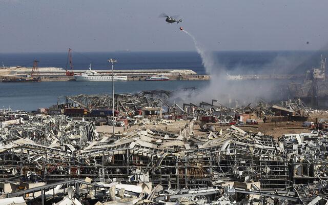 Un hélicoptère de l'armée libanaise largue de l'eau sur la scène de l'explosion qui a frappé la zone du port de Beyrouth, au Liban, le 5 aout 2020. (Hussein Malla/AP)