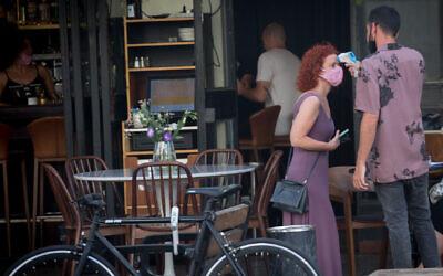 On contrôle la température d'une femme à Tel Aviv, le 4 août 2020. (Miriam Alster/Flash90)
