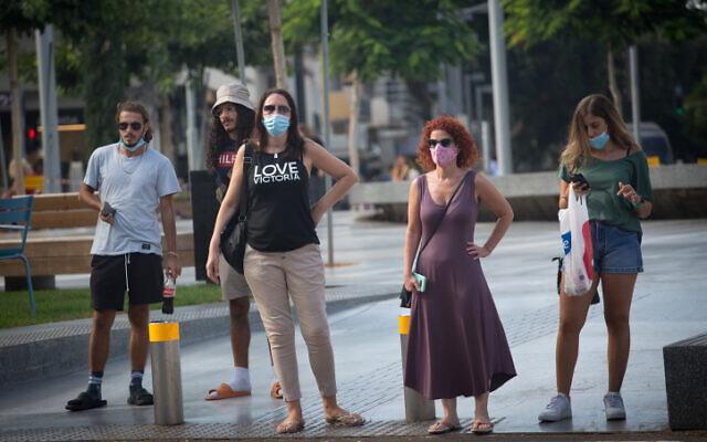 Des israéliens portent des masque de protection à Tel Aviv, el 4 août 2020. (Photo par Miriam Alster/Flash90)